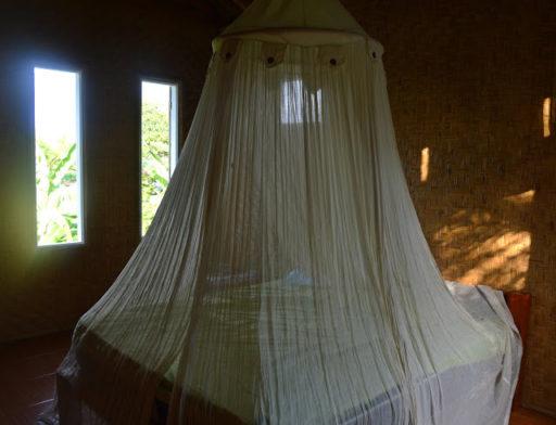 Veľká posteľ, moskitiéra a prírodne zariadený jednoduchý interiér...a ten výhľad!